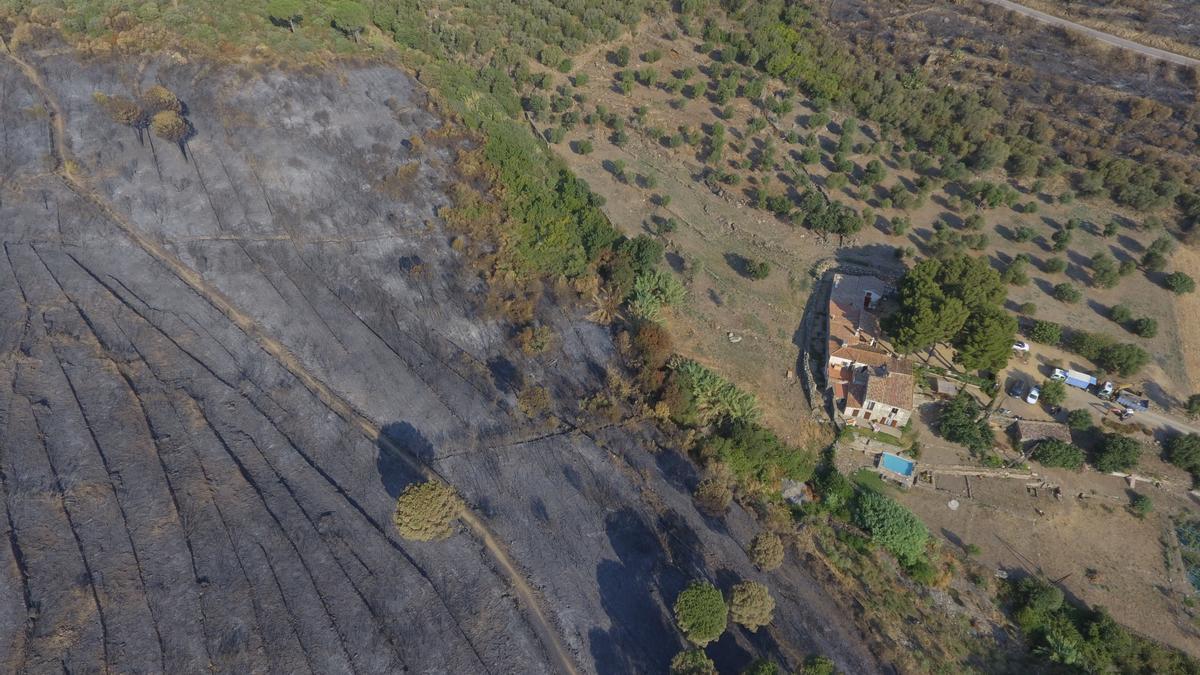 Pla aeri d'una casa de la Vall de la Santa Creu envoltada d'extensió cremada per l'incendi forestal