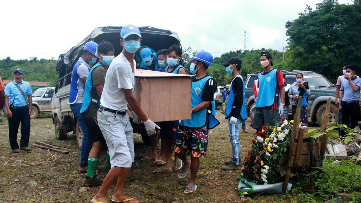 Birmanos llevan a un fallecido en un ataúd.