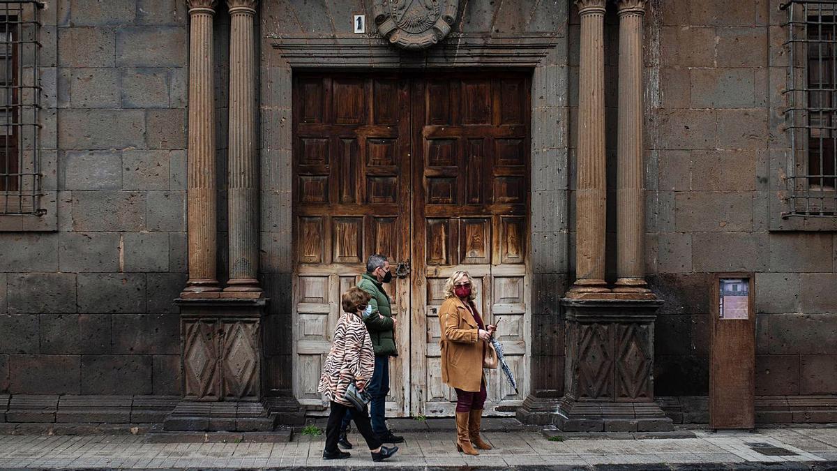 Tres personas caminan por la calle San Agustín de La Laguna.