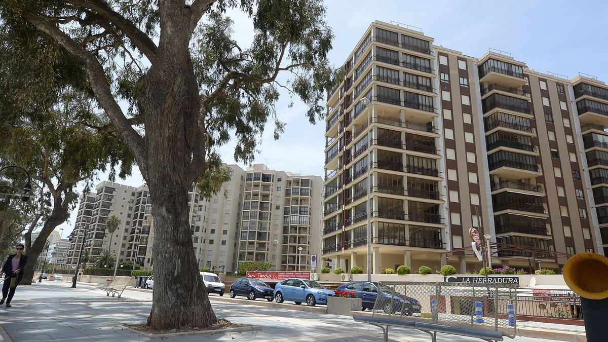 Una mujer pasa frente a varios bloques de apartamentos en Benicàssim