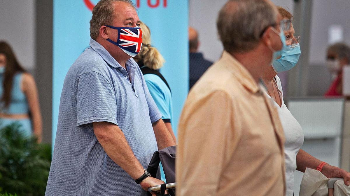 Varios pasajeros británicos a su llegada al aeropuerto Tenerife Sur.     CARSTEN W. LAURITSEN