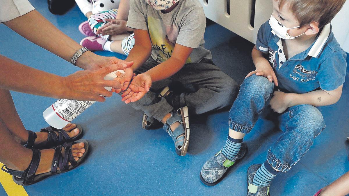 Escolares con mascarilla se desinfectan las manos.