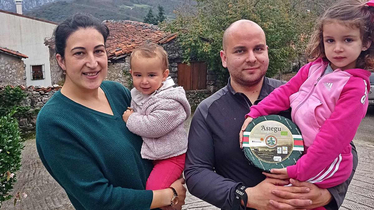 Rocío Bueno, con la pequeña Amaia en brazos, y Pablo Ruiz, con su hija Vega. En el círculo, una pieza de cabrales ecológico con el doble sello en el etiquetado. | Eva San Román
