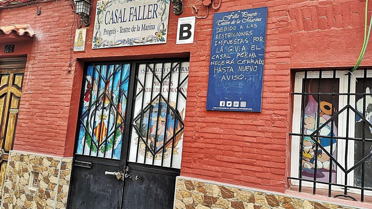 A la izquierda, casal de Progreso-Teatro de la Marina, cerrado «hasta nuevo aviso». A la derecha, el «nuevo» cartel de Fallas.    LEVANTE-EMV