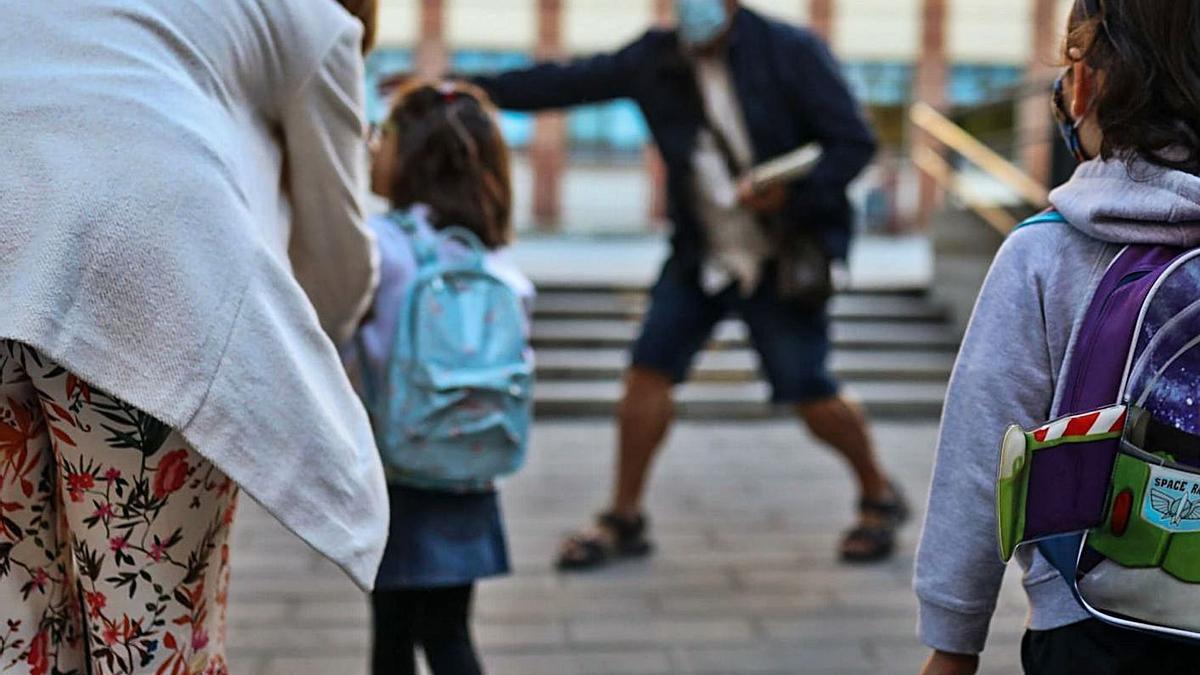 Un profesor organiza la entrada de los niños el primer día de clase del curso pasado.
