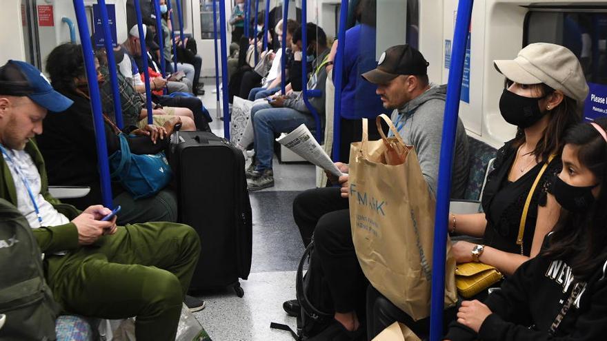 Pasajeros con y sin mascarilla en el Metro de Londres.
