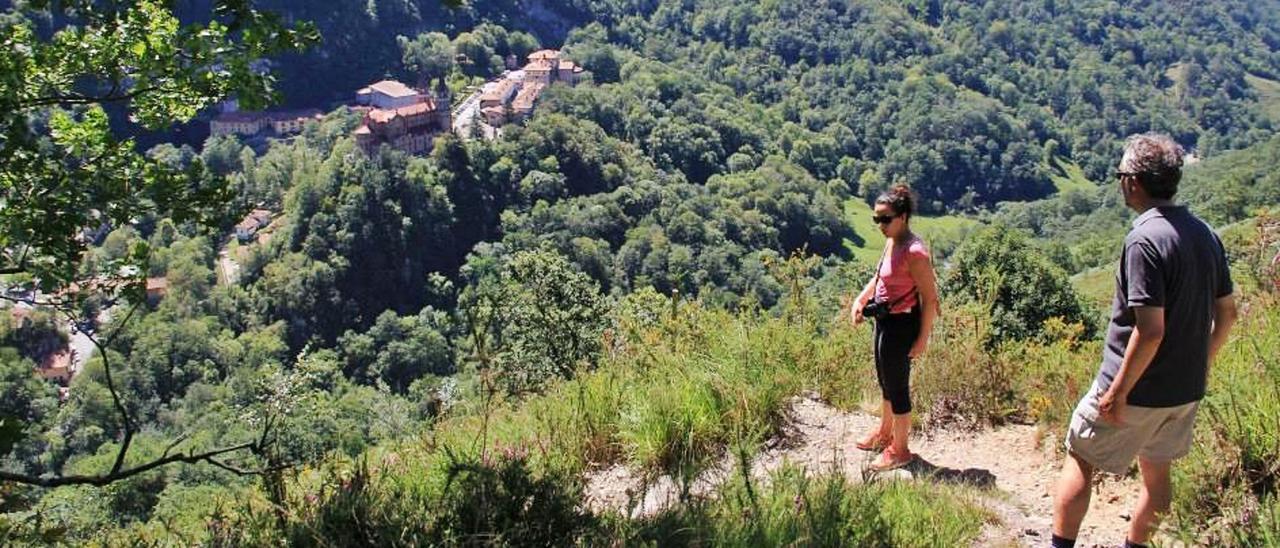Dos turistas descienden de la  Cruz de Priena hacia Covadonga.
