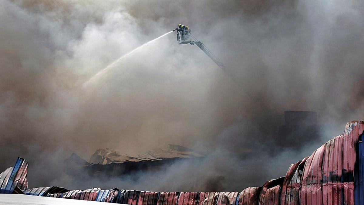 Un bombero intenta controlar el fuego en el parque empresarial de O Ceao el pasado sábado. |   // ELISEO TRIGO