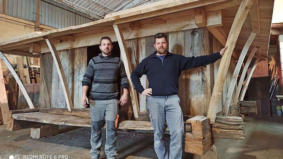 Alfredo y Julio Ovín, con el hórreo de Cadavedo restaurado.   Carpintería Ovín
