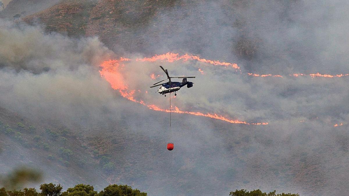 Un helicòpter col·labora en les tasques d'extinció de l'incendi de Sierra Bermeja.   EFE
