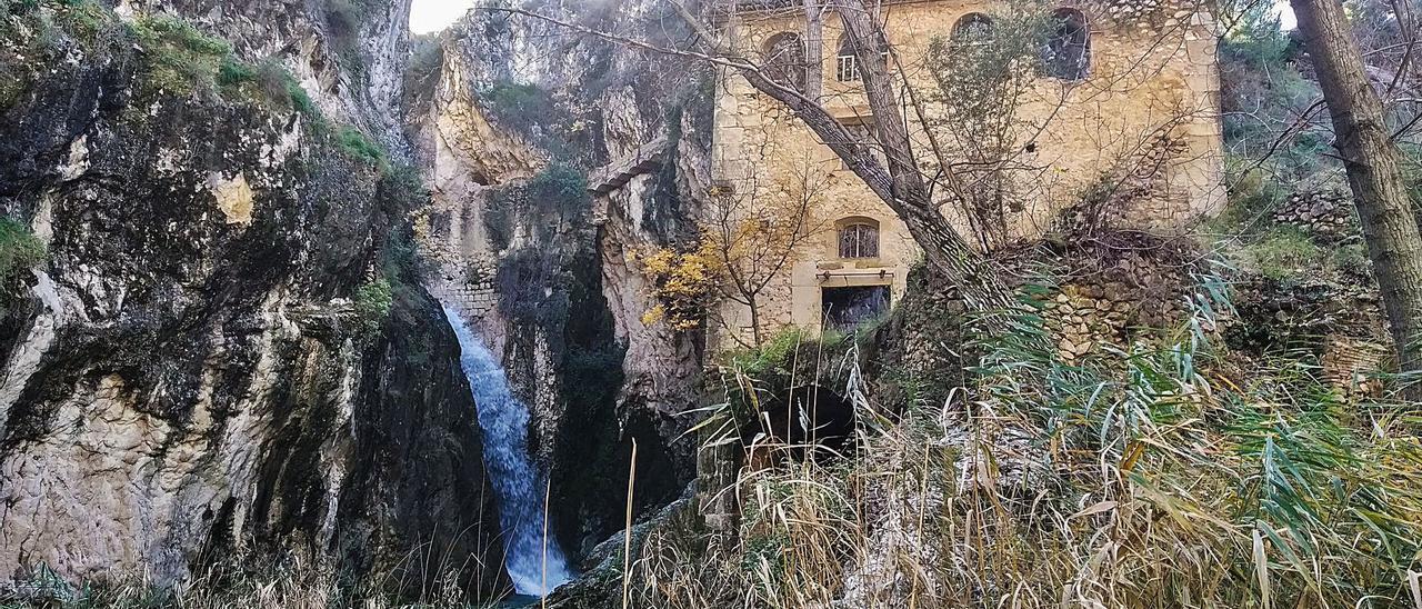 Molí del Salt de Benilloba, con las ruinas del inmueble a cuyo deterioro se quiere poner fin, y la cascada del río Frainos.