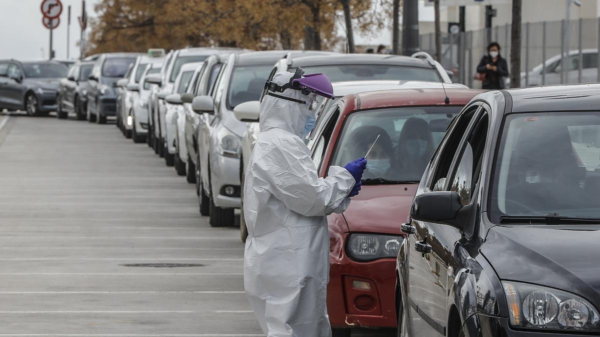 Una trabajadora sanitaria realiza pruebas PCR a una fila de ocupantes de vehículos