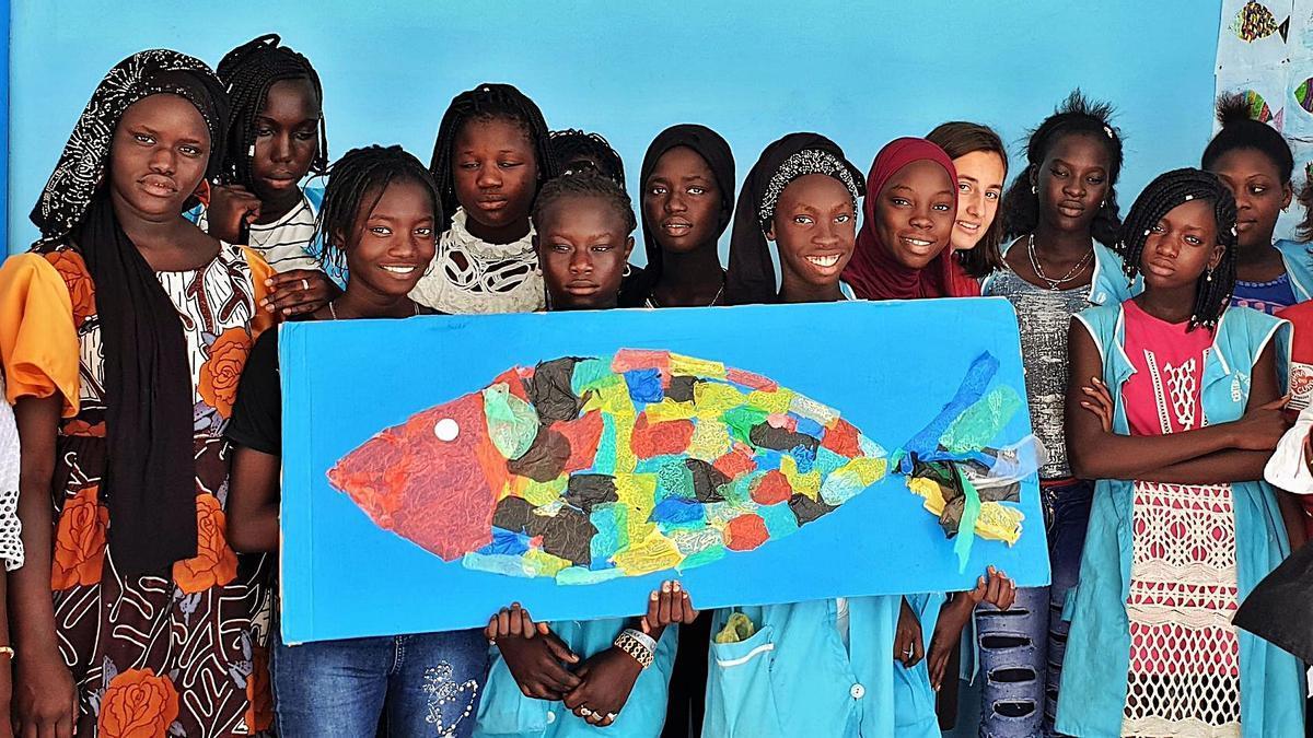 Alumnas de la Escuela Coruña en Senegal, con el pez elaborado con plásticos recogidos de la costa. A la derecha, Guillermo Fernández-Obanza, de Ecodesarroio.  | // ECODESARROIO GAIA