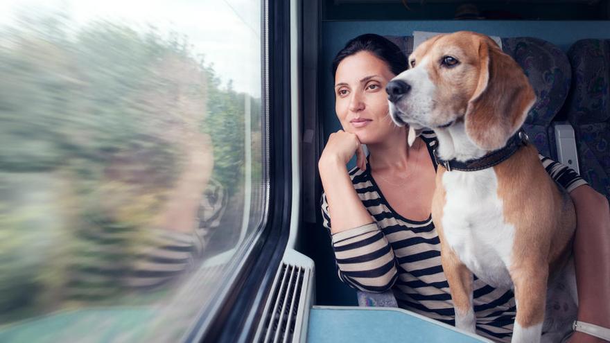 Una mujer viaja con su perro en un tren.