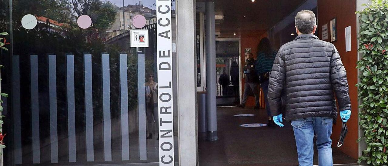 Un empleado público, en la puerta de acceso a la Xunta, en San Caetano.    // XOÁN ÁLVAREZ