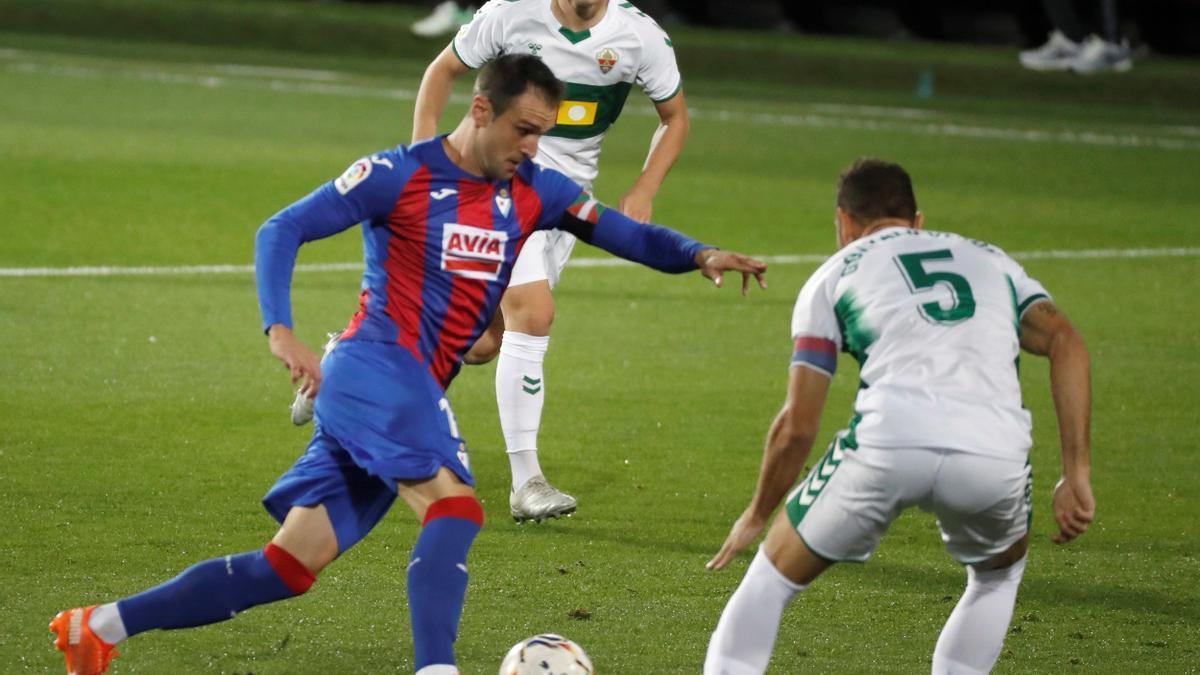 El jugador del Eibar Kike García pelea por el balón ante Gonzalo Verdú