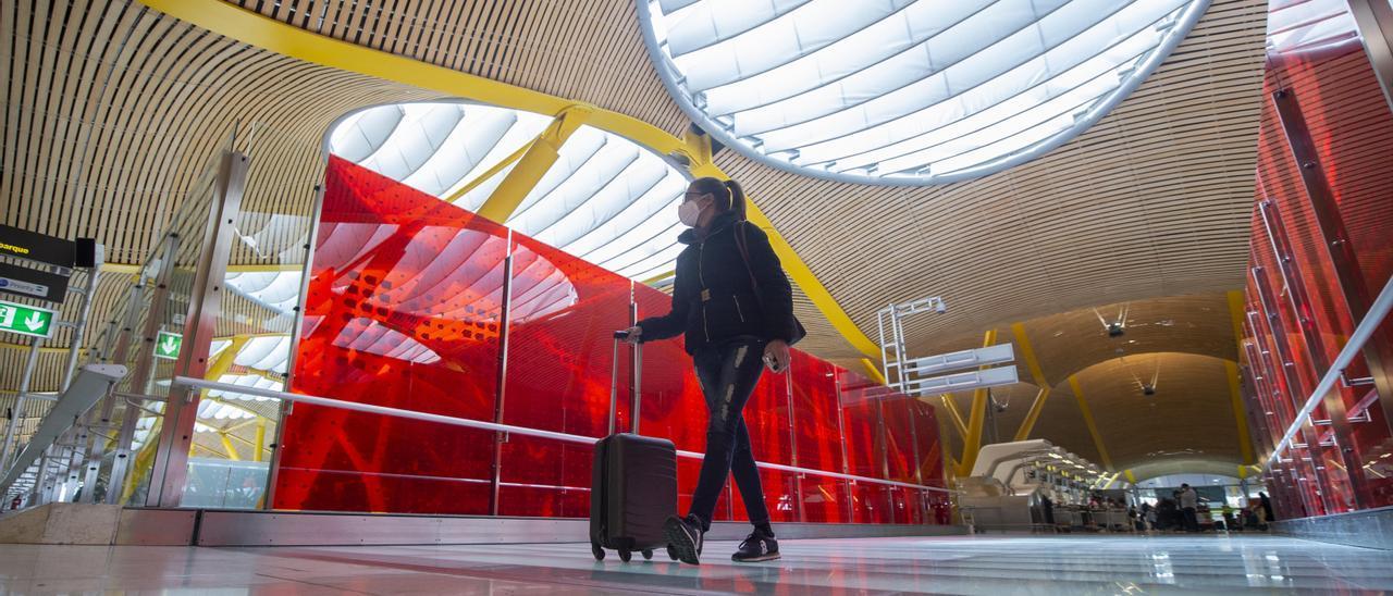 Una joven desplaza su maleta por las instalaciones de la T4 del Aeropuerto Adolfo Suárez Madrid-Barajas.
