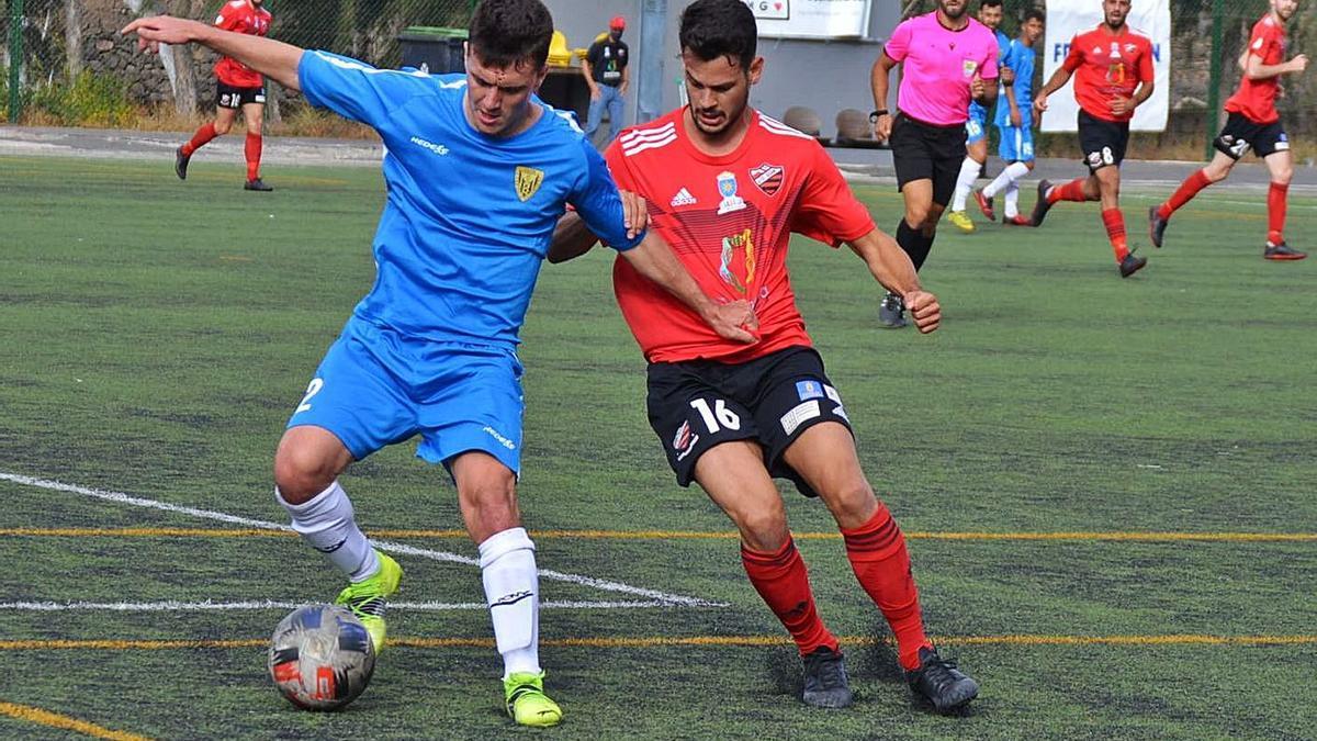 Melo, de la UD Guía, intenta robarle un balón a Rober, zaguero del Atlético Tacoronte, ayer en el Octavio Estévez. | | ARIANNA MOLINA