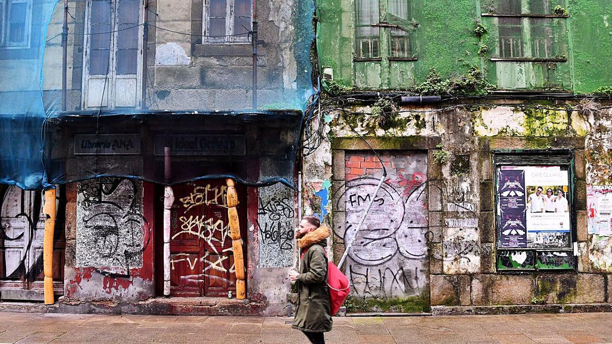 Un vecino pasea frente a dos edificios ruinosos en la calle Orzán. |   // CARLOS PARDELLAS
