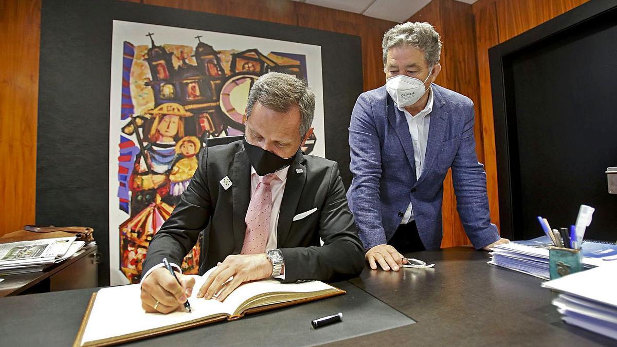 El delegado del Gobierno en Galicia, José Miñones, firma en el libro de honor del Concello. |   // R.V.