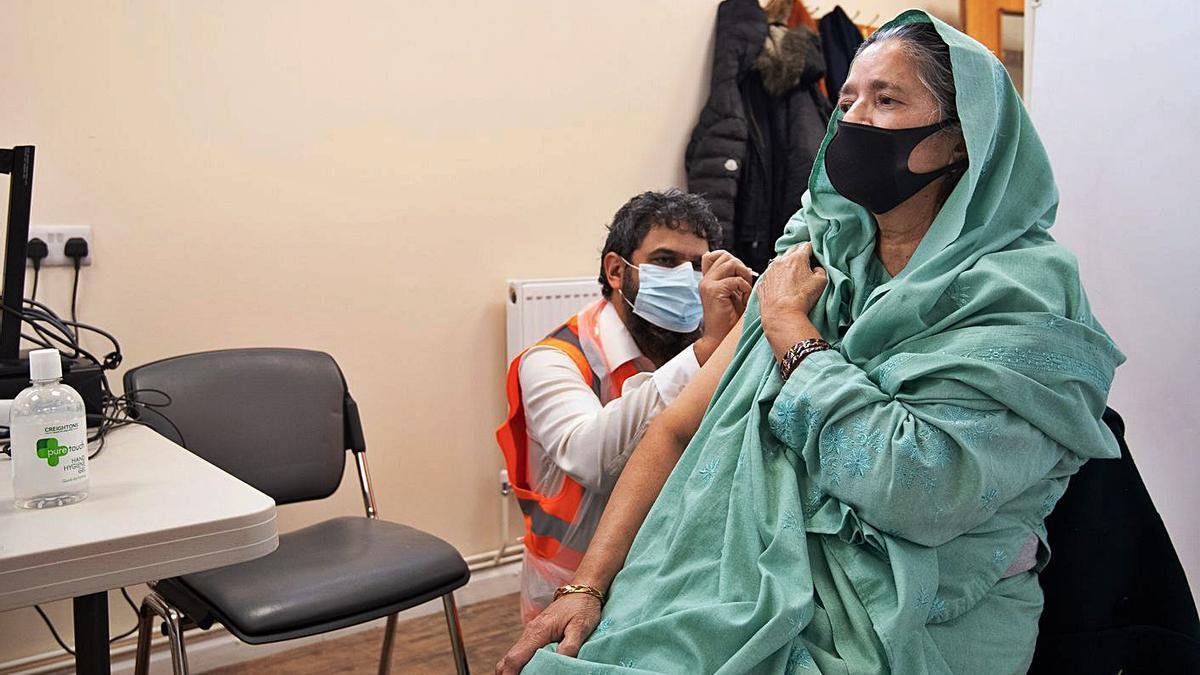 Una mujer, ayer mientras es vacunada contra el COVID en Reino Unido. |   // EFE