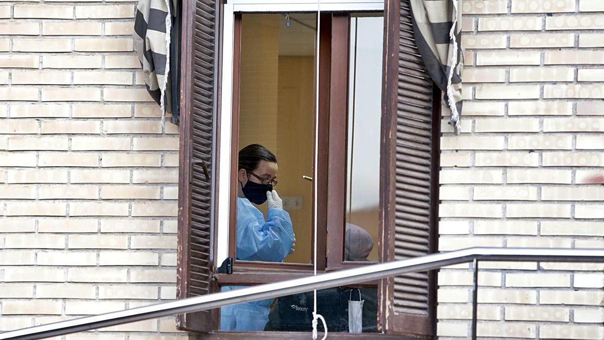 Un trabajadora del Asilo Santa Marta, con el equipo de protección, atendiendo ayer a un residente.