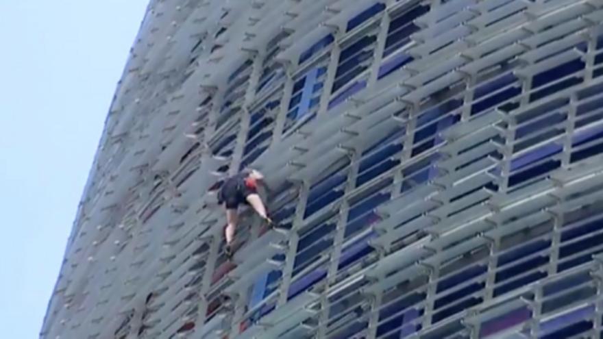 Un hombre escala la Torre Glòries de Barcelona mientras otros dos lo graban