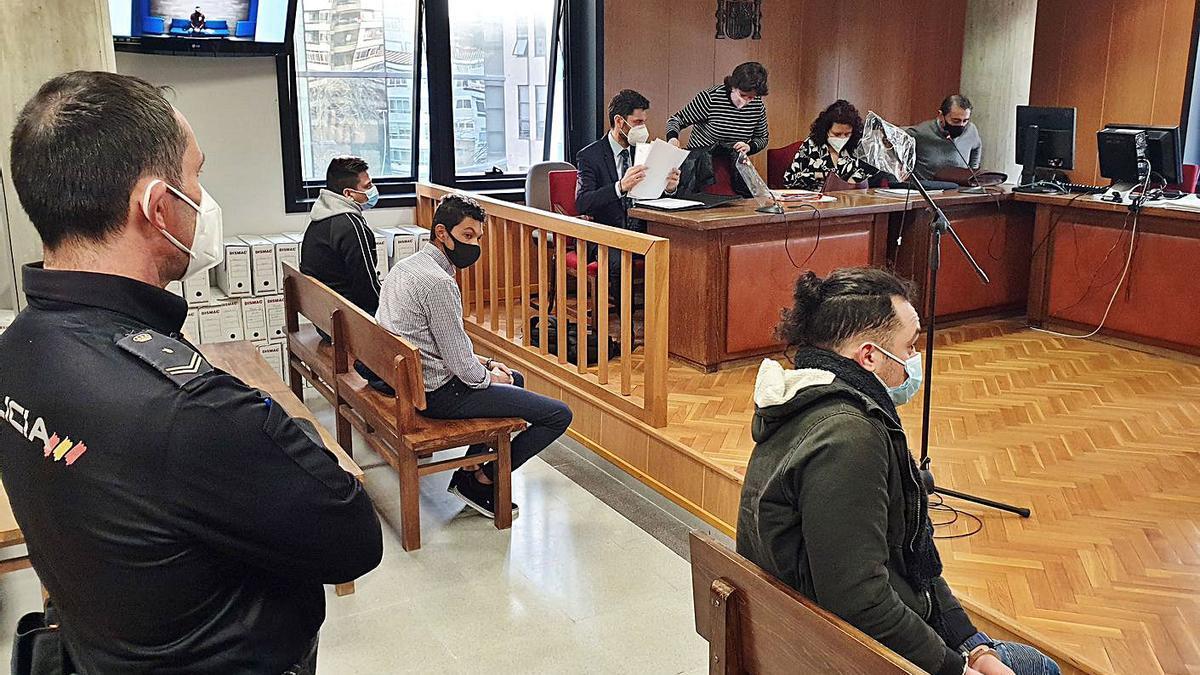 Tres de los acusados en los banquillos del juzgado de Vigo y el cuarto, en la pantalla de la izquierda ya que compareció por videoconferencia desde la prisión de Monterroso (Lugo).  // MARTA G. BREA