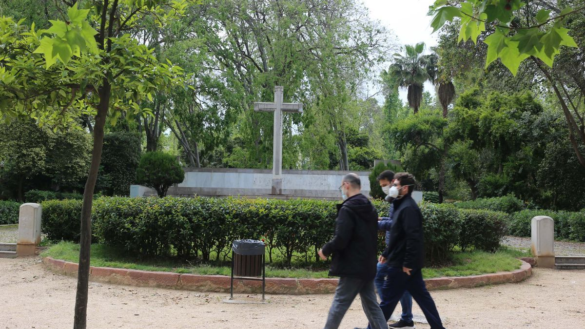 Tres personas transitando ayer por delante de la cruz de los caídos ubicada en el parque Ribalta de Castelló.