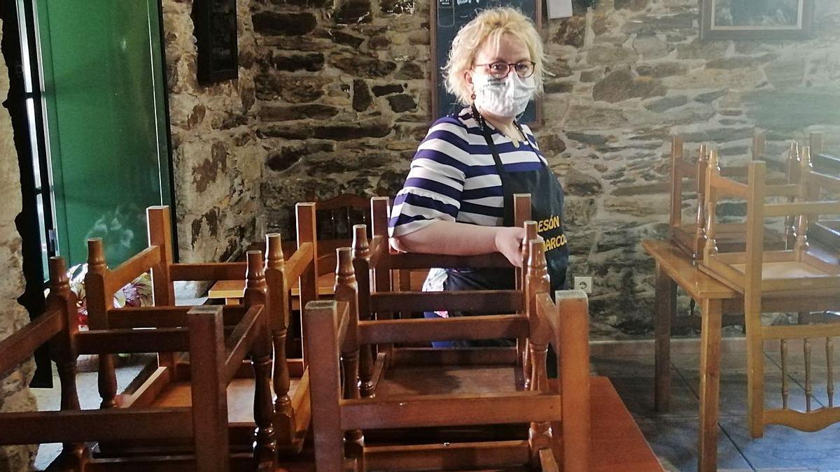 La propietaria del Mesón San Marcos, ayer, dentro del local, con las sillas recogidas.   | // LA OPINIÓN