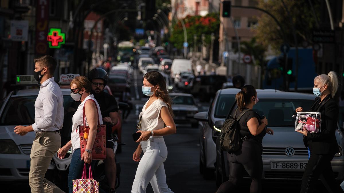 Varias personas con mascarilla caminan por la capital tinerfeña.