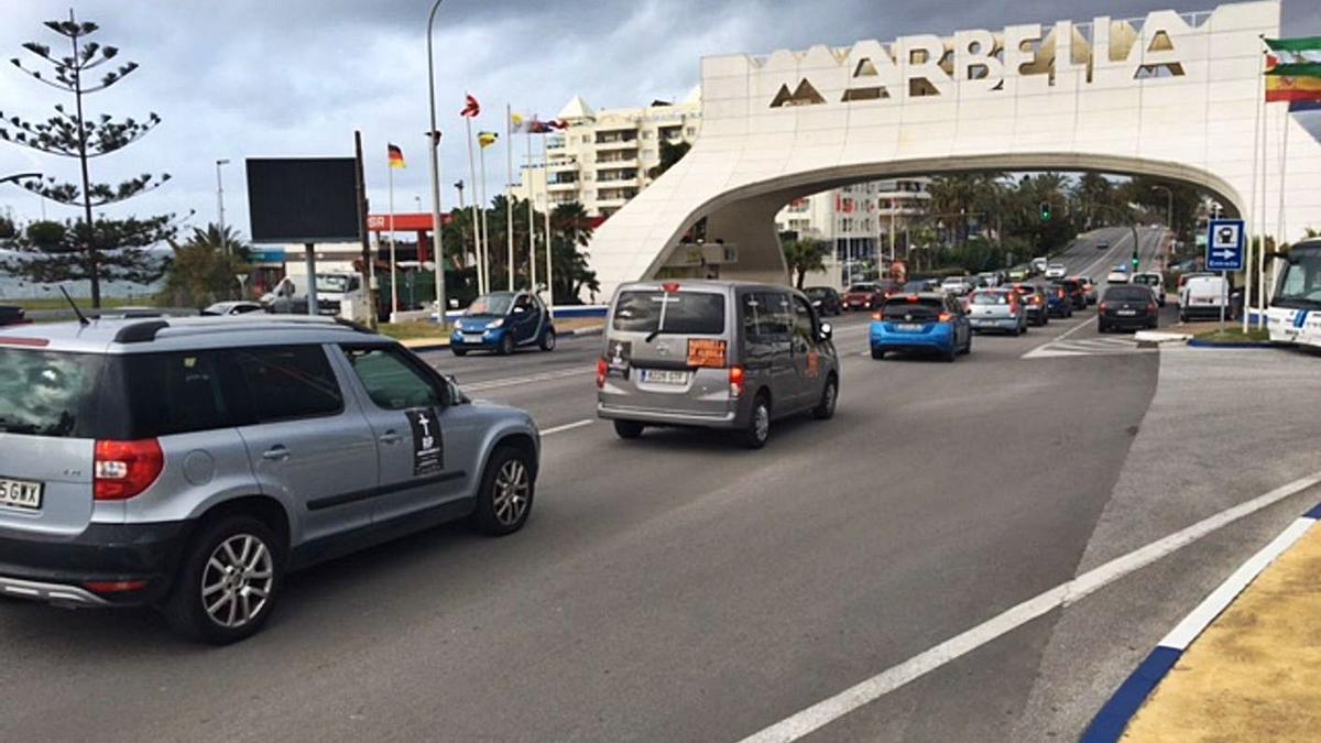 Parte de los vehículos de la caravana reivindicativa pasa por el Arco de Marbella.   L. O.