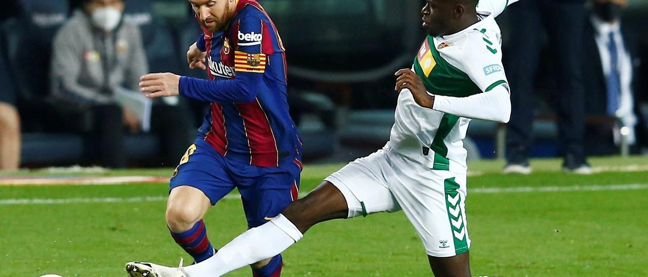 Mfulu corta un balón a Leo Messi durante un partido del Elche contra el Barcelona