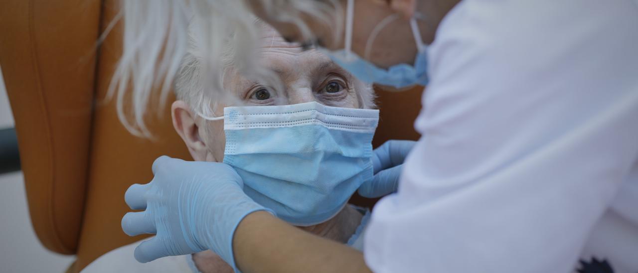 Una mujer con mascarilla en una residencia de mayores.
