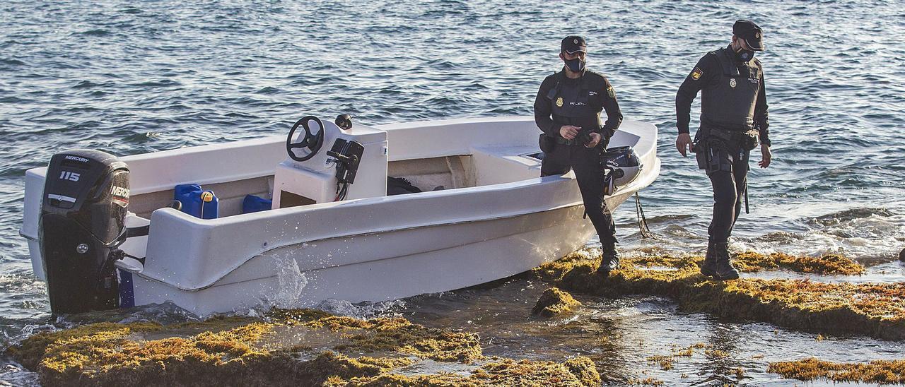 Dos policías nacionales con una patera que llegó el pasado marzo al Cabo de las Huertas, en Alicante.   ALEX DOMÍNGUEZ