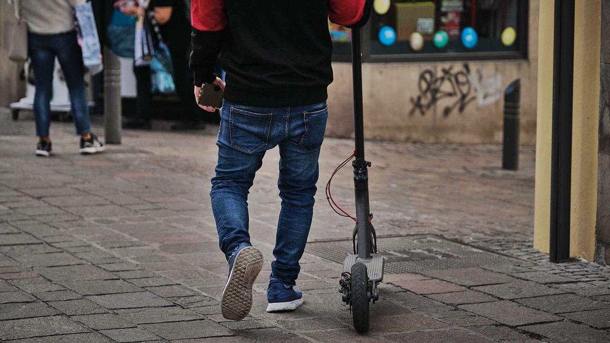 Un joven en patinete por una calle de Santa Cruz.