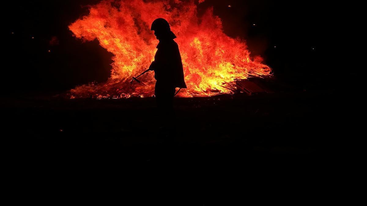 Un bombero pasa cerca de una hoguera de San Juan, en Santa Cruz de Tenerife.