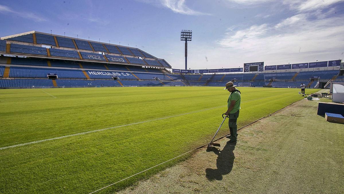 Uno de los jardineros que trabaja en el mantenimiento del césped del estadio acondiciona la zona de los banquillos con todo el campo en silencio y vacío.