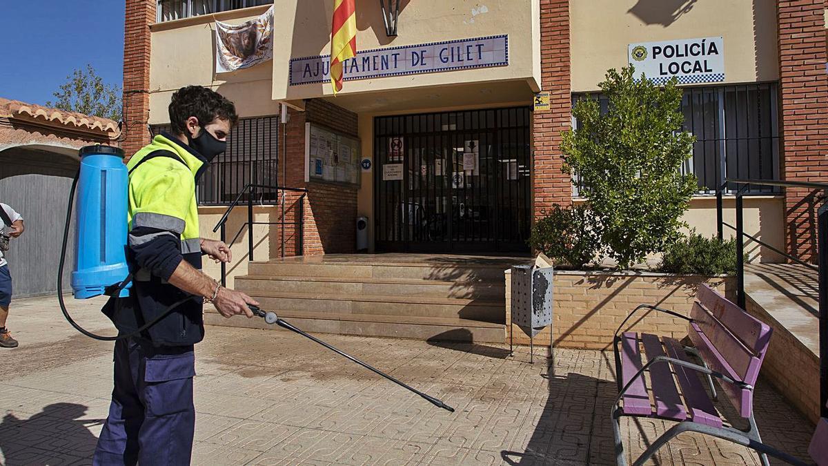 Un momento de la fumigación ayer del exterior del  Ayuntamiento de Gilet tras conocerse el positivo del alcalde y de una trabajadora. | DANIEL TORTAJADA