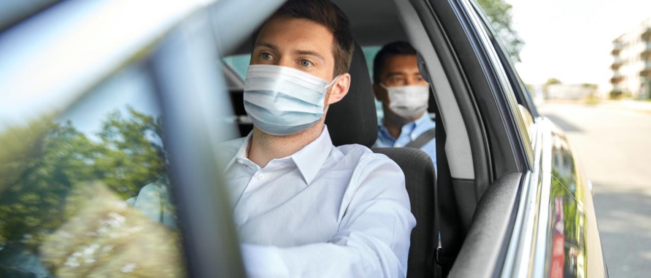 Un hombre, con mascarilla en su vehículo