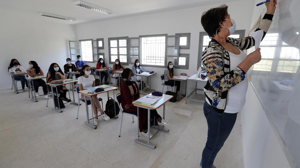 Una maestra da clase en un aula