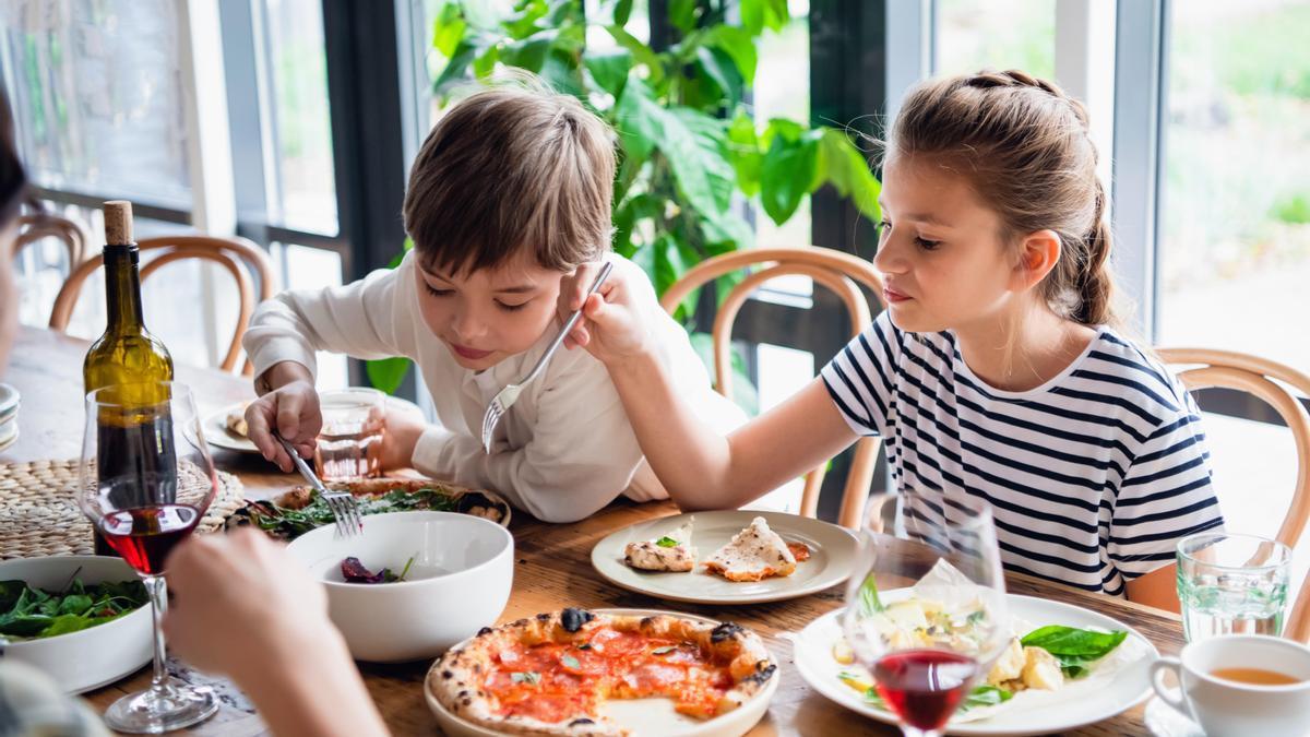 Dos niños sentados a la mesa para comer