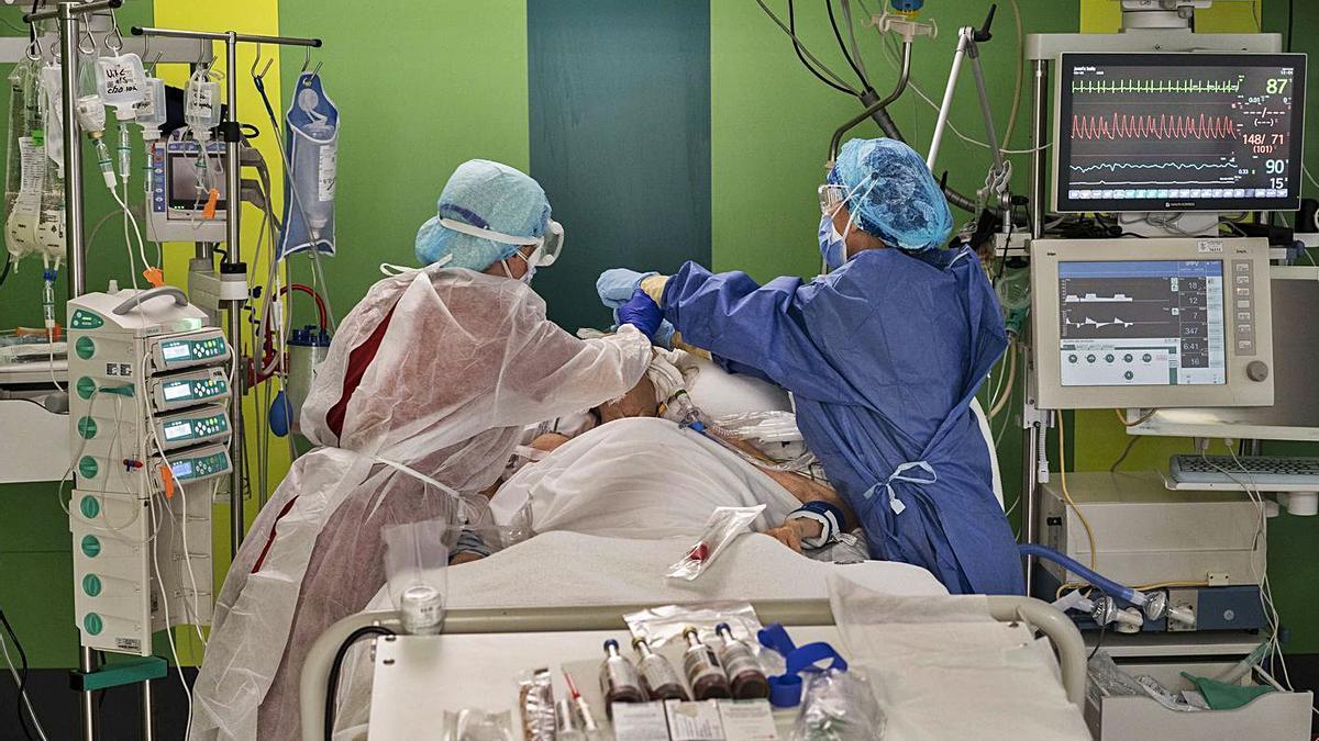 Dos sanitarias atienden a un paciente en la UCI del Hospital General durante la segunda ola. | GERMÁN CABALLERO