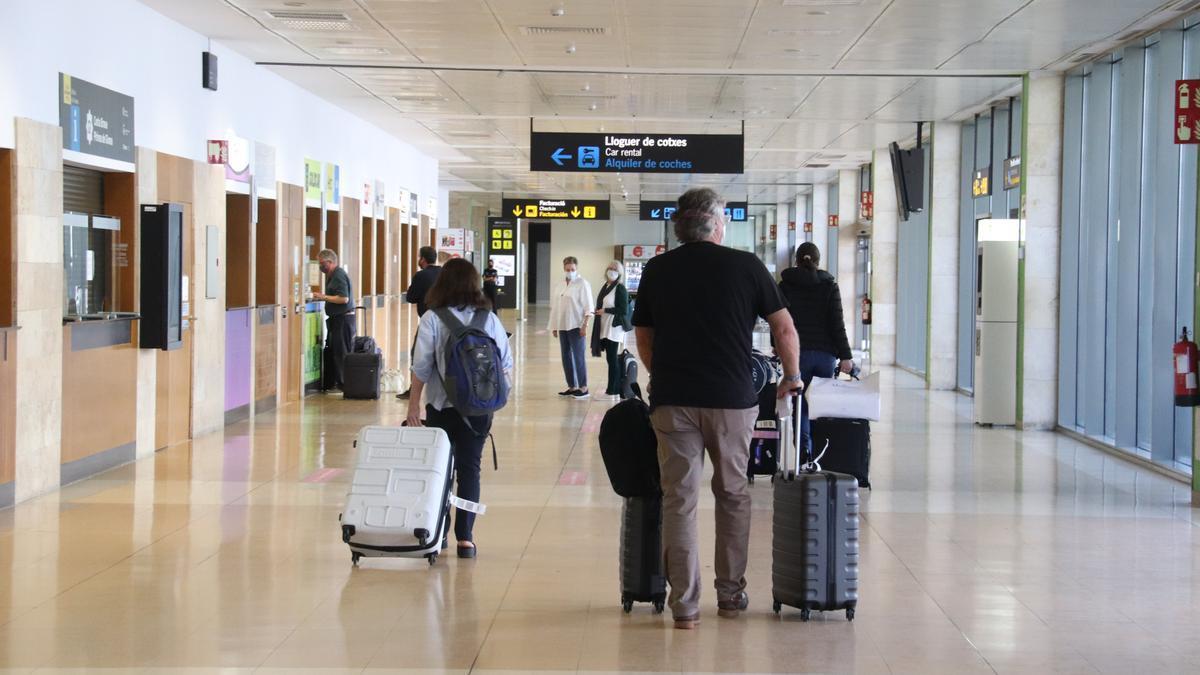 Pla obert de diversos passatgers a l'aeroport de Girona carregats amb maletes a la zona d'arribades