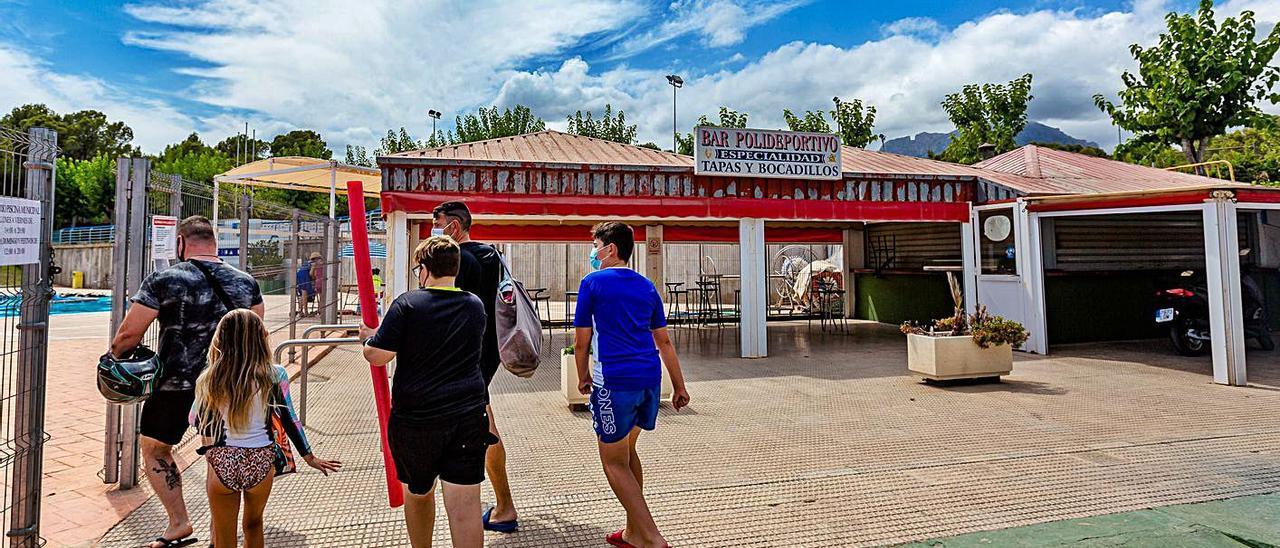 Usuarios de la piscina municipal entran a la instalación frente a uno de los bares cerrados