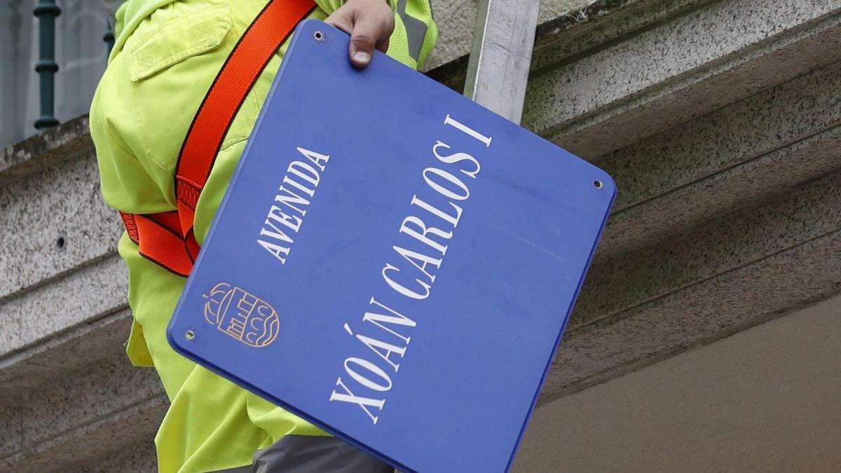 Un operario retira una placa de la Avenida 'Xoan Carlos I'.