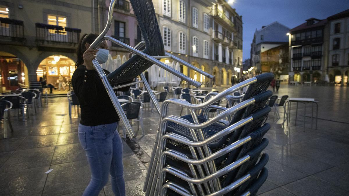 Una trabajadora recoge una terraza en Avilés