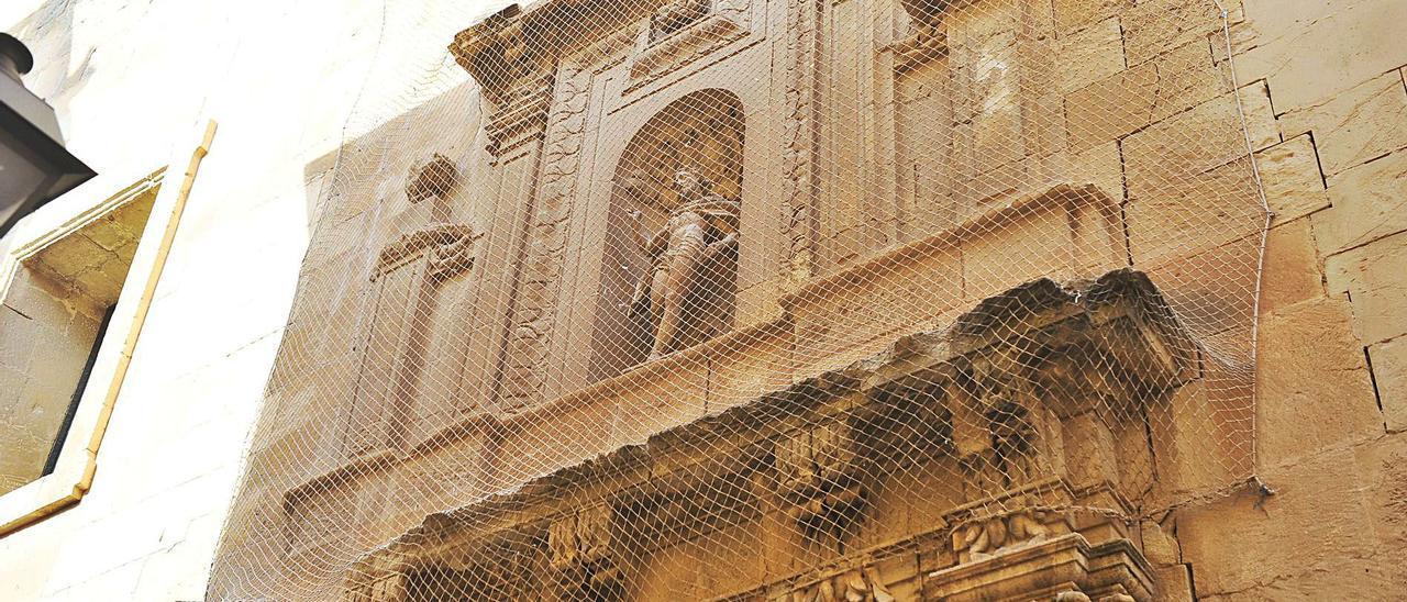 Una de las redes que protegen la basílica de Santa María ante el gran estado de deterioro que presenta la casa del Misteri.  