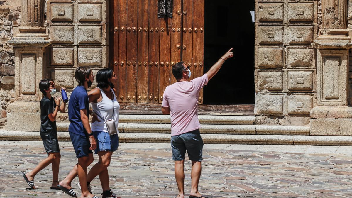 Cuatro turistas pasean ayer por la mañana por la plaza de Santa María de Cáceres frente al Palacio Episcopal.