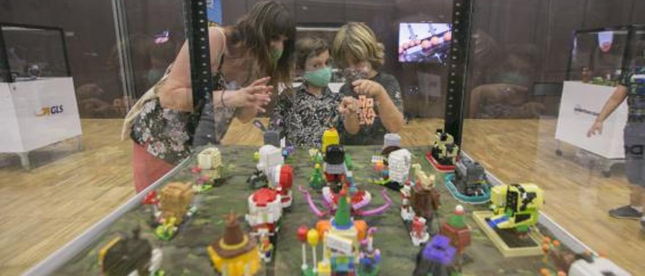 Una mujer y dos niños, ante los Lego. | ÀLEX OLTRA